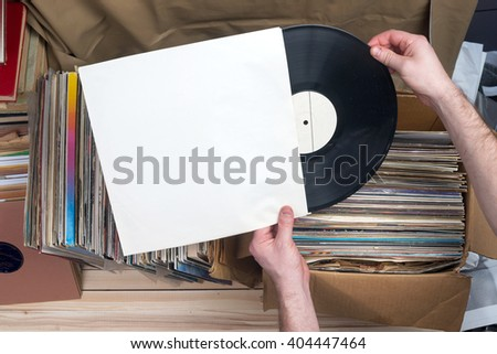 Retro styled image of a collection of old vinyl record lp\'s with sleeves on a wooden background. Browsing through vinyl records collection. Music background. Copy space.
