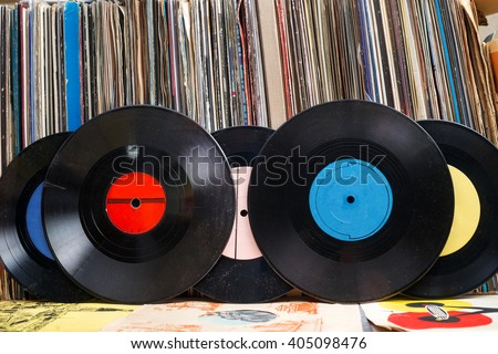 Retro styled image of a collection of old vinyl record lp's with sleeves on a wooden background.  Copy space. #405098476