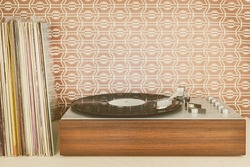 Retro styled image of a vintage record player with record albums in front of seventies wallpaper