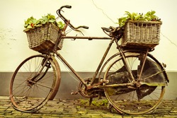 Retro styled image of an old broken rusty bicycle with baskets