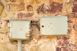 Retro styled junction boxes. Old controlled power system mounted on Natural Stone Wall. Control box. Electric system. Industrial background. Retro electric power boxes.