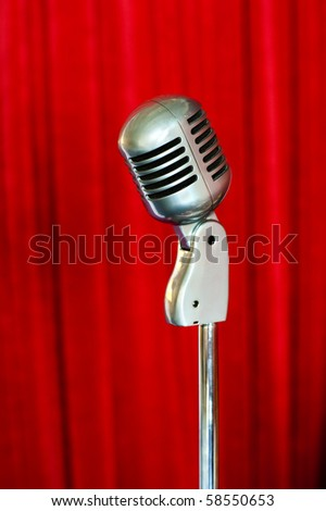 retro styled microphone on crimson velvet curtain background