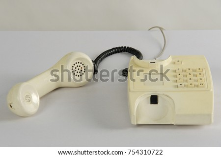 Retro styled/ old fashioned white telephone on the table in studio.