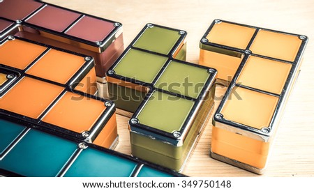 Retro styled or retro color geometric shapes of four square blocks on wooden surface. Concept of classic puzzle game. Isolated on white background. Slightly de-focused and close-up shot. Copy space.