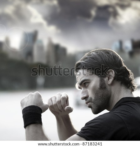 Retro styled photo of a young sexy man with fists up ready to fight against city background and dramatic sky