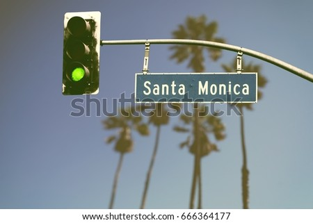 Retro styled Santa Monica Boulevard road sign with defocused palm trees in background #666364177