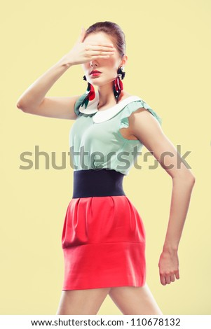 Retro styled young woman covers her eyes with one hand. She's wearing big fancy earrings and red mini, yellow background
