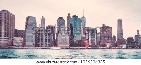 Retro stylized panoramic picture of the Manhattan skyline at sunset, New York City, USA.