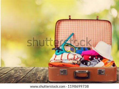 Retro suitcase with travel objects on wooden #1198699738