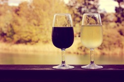 Retro sunset filter style image of two glasses of wine, white and red, on wooden rail with country rural scene in background.