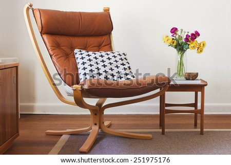 Retro tan leather chair and side table with flowers interior #251975176