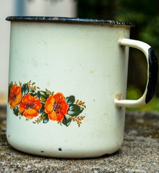 Retro tea cup made from tin material.Red an Orange Flower pattern and ornament text.A rusted vintage enamel mug.Heavy duty metal mug.Enamel porcelain mug in summer nature.Enameled mug with dry flower.