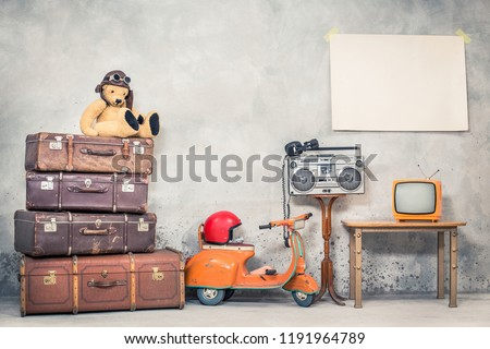 Retro Teddy Bear toy in aviator's hat, aged travel valises, children's pedal scooter, helmet, cassette boombox with headphones, TV, paper poster blank on concrete wall. Vintage style filtered photo