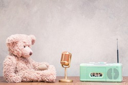 Retro Teddy Bear toy with golden microphone and outdated fm radio cassette recorder front concrete wall background. Listening nostalgic music concept. Vintage old style filtered photo