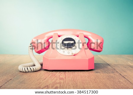 Retro telephone front mint green wall background. Old style filtered photo #384517300