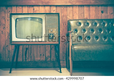 Retro television and vintage sofa with vintage wooden background. Classic vintage style home decoration. Retro style concept. #429998707