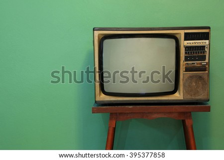 Retro television on old wooden deck with vintage green background. #395377858
