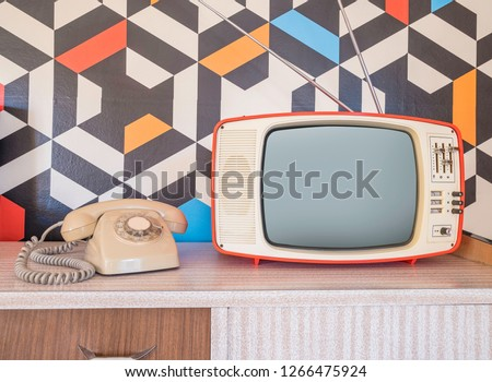 Retro television with vintage telephone and wallpaper in the background. Template interior decoration with ceramic decoration from the 70s Photo stock ©