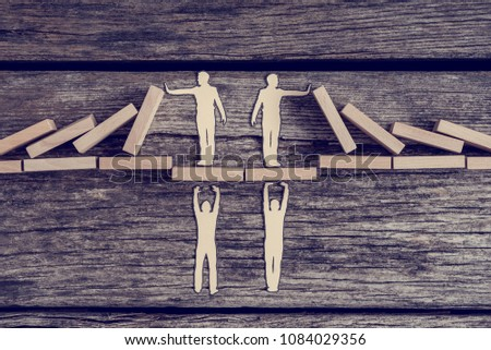 Retro toned image of two paper cutouts of men supporting others on a bridge while they prevents domino effect. #1084029356