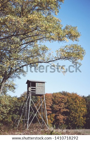 Retro toned picture of a wooden deer hunting pulpit at the edge of a forest and field.