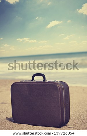 Retro travel suitcase is alone on a beach