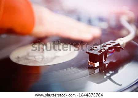 Retro turntable plays vinyl record with music.Professional hip hop dj scratches records on party in nightclub.Disc jockey playing musical tracks on festival in night club.Pro concert audio equipment
