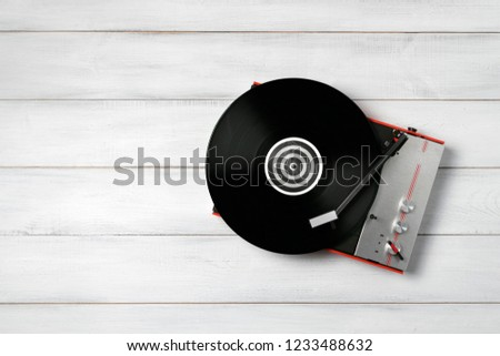 Retro turntable vinyl record player on the background white wooden boards. Sound technology for DJ to mix & play music. Needle on a vinyl record. Black vinyl record #1233488632