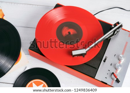 Retro turntable vinyl record player on the background white wooden boards. Sound technology for DJ to mix & play music. Needle on a vinyl record. Red vinyl record. Black vinyl record #1249836409