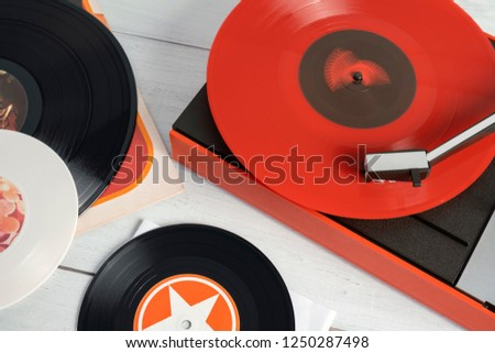 Retro turntable vinyl record player on the background white wooden boards. Sound technology for DJ to mix & play music. Needle on a vinyl record. Red vinyl record. Black, white vinyl record #1250287498