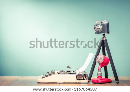 Retro typewriter, outdated film photo camera on tripod and old microphone on wooden table front mint green wall background. Blogging concept. Vintage style filtered photo