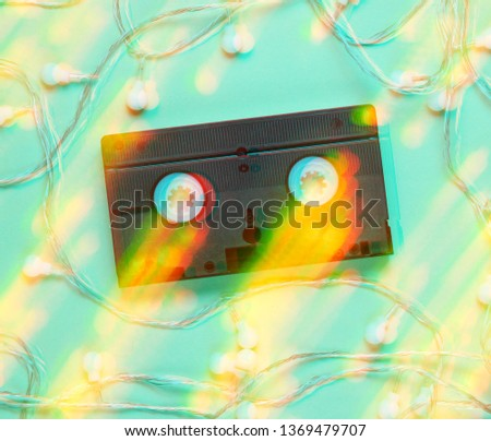 Retro vhs video tape with bright glowing led garlands on blue background.Gitch effect.  Light effect Top view, minimalism #1369479707