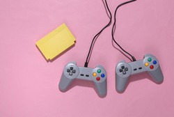 Retro video game cartridge and joysticks on pink bright background. Top view