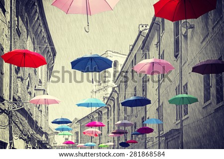 Retro vintage filtered colorful umbrellas hanging above street of Ferrara, black and white background.