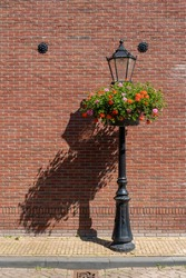 Retro vintage lamp and lantern is made of cast iron. Historical illumination on the street during sunny daylight, brick wall in the background.