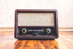 Retro vintage radio. Music nostalgia with old 60s style song player. Dusty speaker and receiver on wood. Knobs and frequency tuner, front view. Stereo sound technology for news broadcast or propaganda