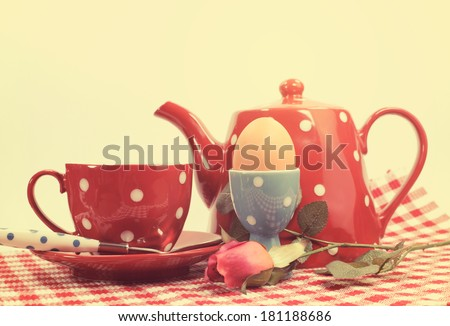 Retro vintage red check Happy Mothers Day or romantic Valentine breakfast with tea cup tea pot and egg in red and blue polka dot 1950s style china