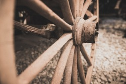 Retro vintage sepia image of a disused old wooden cart wheel