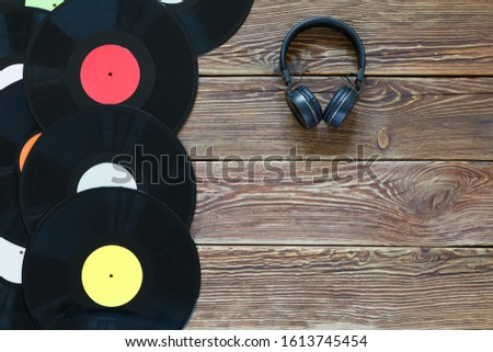 Retro vinyl discs records and headphones on wood table background. Multicolored labels. Top view. Place to copy space. Horizontally framed shot.
