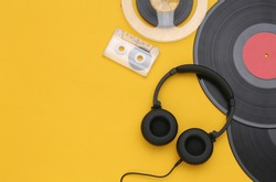 Retro vinyl records, audio magnetic reel, audio cassette and stereo headphones on yellow background. Copy space. Top view