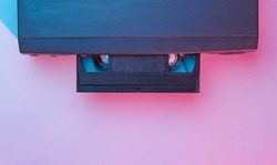 Retro wave, minimalism 80s concept. Video player with vhs cassette, neon light. Night life. Top view