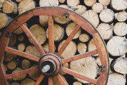 Retro wheel photo. Pieces of wood and wagon wheel. Old cart wheels .Vintage wooden carriage wheel,  wood background. Old wooden carriage wheel hanging on the barn
