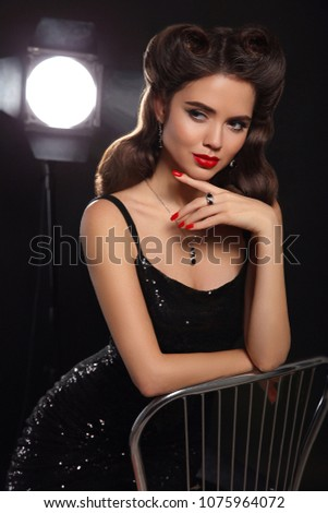 Retro woman portrait with red lips makeup, curls hair style, manicured nails and jewelry set. Brunette actress posing over black background with studio back lights.