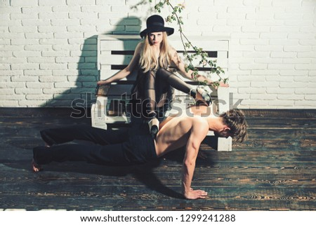 retro woman put legs on back of muscular man. muscular man training sport at pretty young girl. couple in love of guy with bare chest and girl in retro hat. romantic dominating relations and poetry.