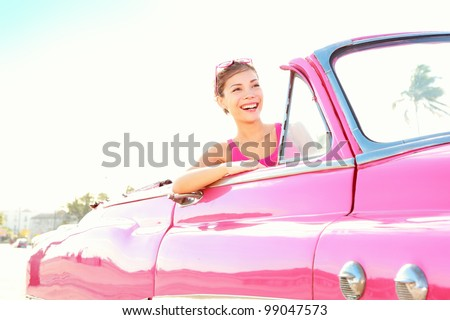 Retro woman smiling happy in old pink vintage car driving on road trip on beautiful summer day. Pretty multiracial Asian / Caucasian female model