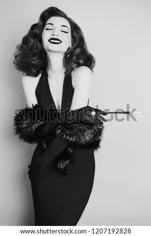 Retro woman with curly hair in black dress and long gloves on gray background. Girl is dressed in retro style with natural fur and the mouthpiece in hand smiling with white teeth. Retro model