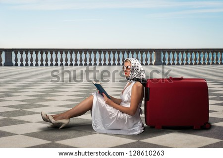 Retro woman with sunglasses and suitcase reading book portrait outdoors in front of the sea.