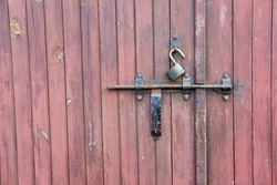 Retro wooden garage door wth padlock and old metal hasp