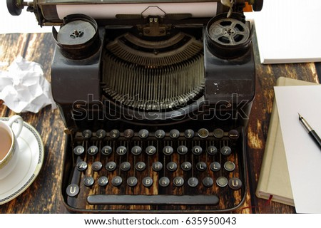 Retro writing machine with style keyboard. Obsolete typewriter on table. #635950043