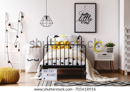 Retro yellow clock on white bedside cabinet in creative kids bedroom with poster on wall