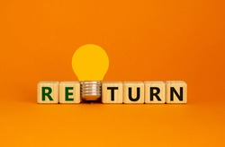 Return symbol. Wooden cubes with word 'return'. Yellow light bulb. Beautiful orange background. Business and return concept. Copy space.